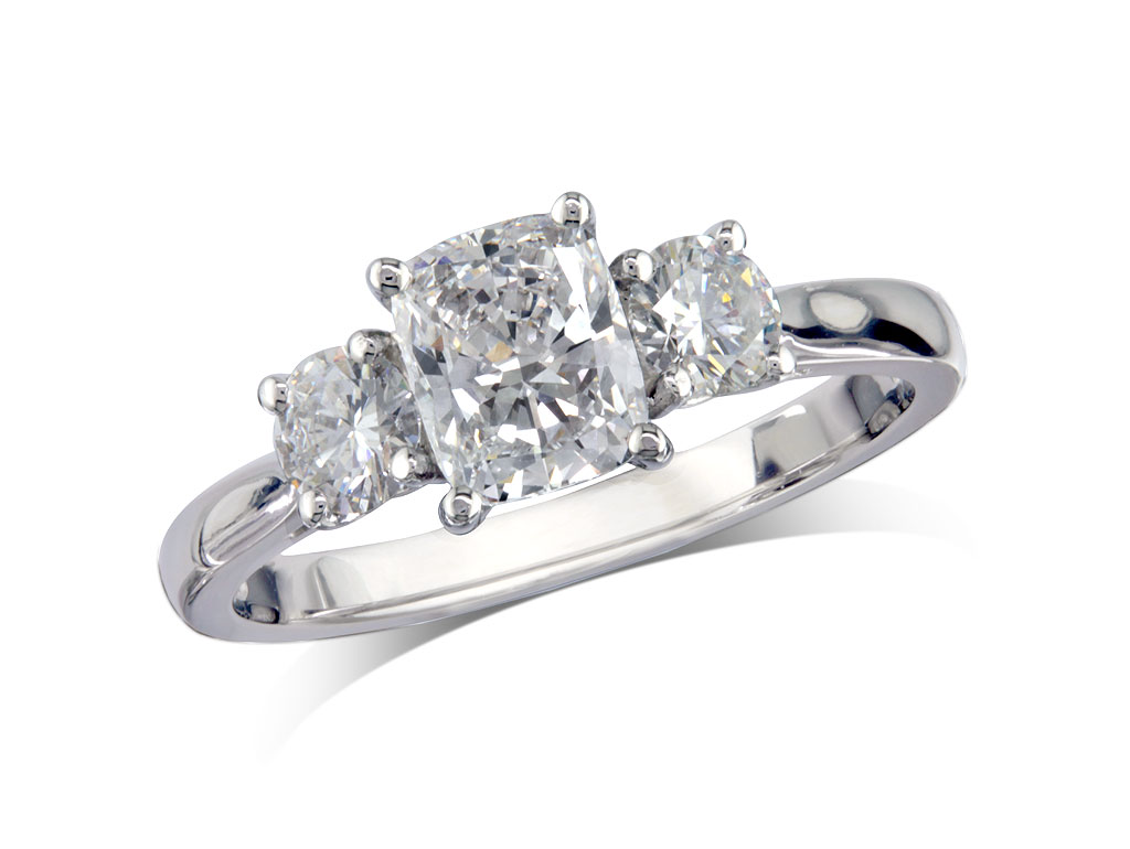 Platinum set three stone diamond engagement ring, with a certificated cushion cut centre in a four claw setting, and one brilliant cut on each shoulder. Total diamond weight: 0.87ct.