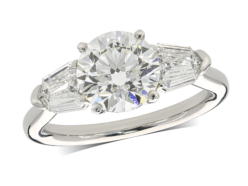 Platinum set three stone diamond engagement ring, with a certificated brilliant cut centre in a four claw setting, and one tapered bagutte cut on each shoulder. Perfect fit with a wedding ring. Total diamond weight: 2.73ct.