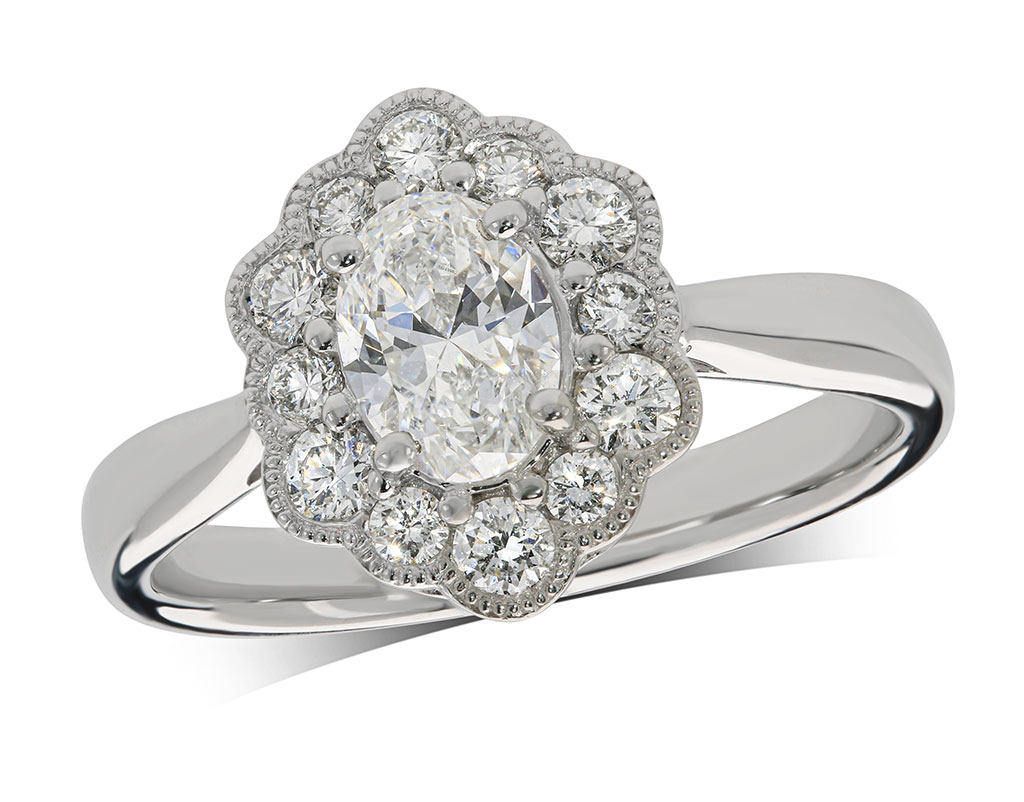 Platinum set diamond ring, with a certificated oval cut centre in a four claw setting, surrounded by a scalloped diamond set cluster. Total diamond weight: 0.99ct.