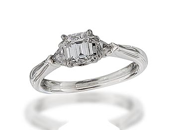 Platinum set three stone diamond engagement ring, with a certificated emerald cut centre in a four claw setting, and one trilliant cut on each shoulder. Total diamond weight: 0.80ct.