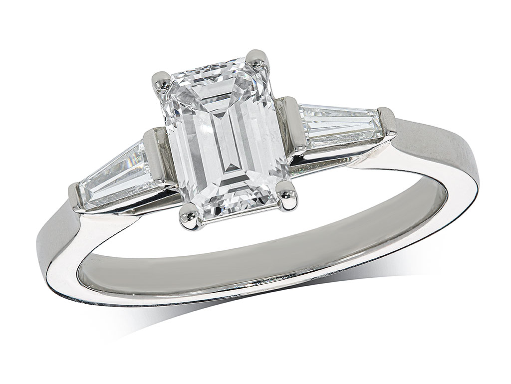 Platinum set three stone diamond engagement ring, with a certificated emerald cut centre in a four claw setting, and one tapered baguette cut on each shoulder. Perfect fit with a wedding ring. Total diamond weight: 1.31ct.