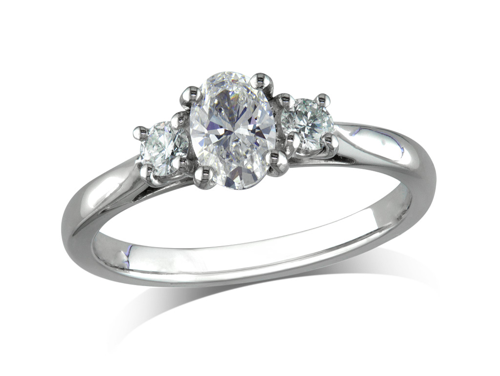 Platinum set three stone diamond engagement ring, with a certificated oval cut centre in a four claw setting, and one brilliant cut on each shoulder. Total diamond weight: 0.42ct.