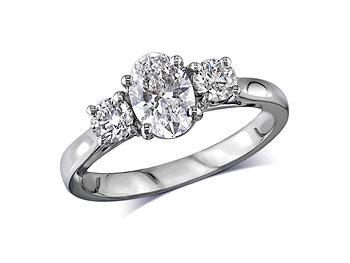 Platinum set three stone diamond engagement ring, with a certificated oval cut centre in a four claw setting, and one brilliant cut on each side with diamond set shoulders. Perfect fit with a wedding ring. Total diamond weight: 1.32ct.