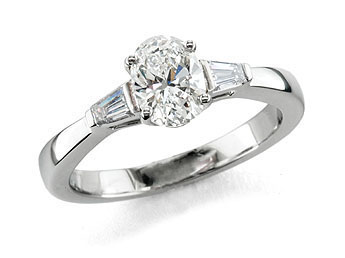 Platinum set three stone diamond engagement ring, with a certificated oval cut centre in a four claw setting, with a tapered baguette cut diamond either side. Total diamond weight: 0.97ct.