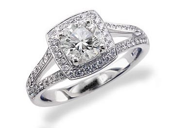 Platinum set diamond engagement ring, with a certificated brilliant cut in a four claw setting, surrounded by a diamond set cluster and split shoulders. Perfect fit with a wedding ring. Total diamond weight: 1.24ct.