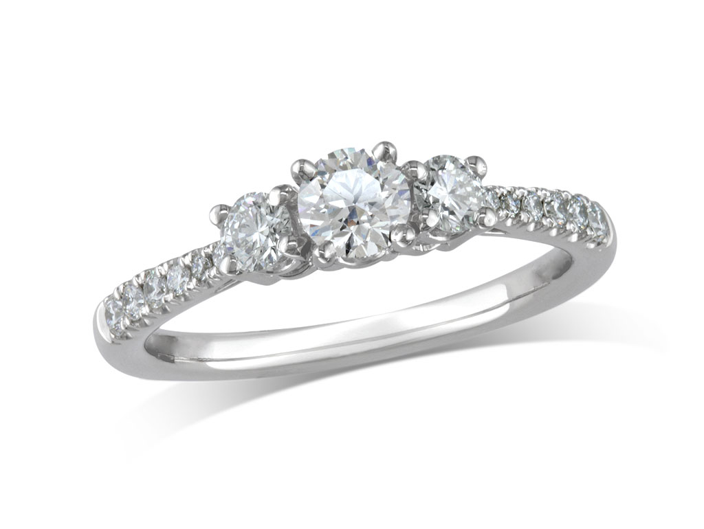 Platinum set three stone diamond engagement ring, with a certificated brilliant cut centre in a four claw setting, and one brilliant cut with diamond set shoulders on each side. Perfect fit with a wedding ring. Total diamond weight: 0.86ct.