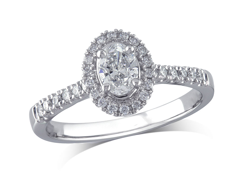 Platinum set diamond ring, with a certificated oval cut centre in a four claw setting, surrounded by a diamond set cluster and shoulders. Perfect fit with a wedding ring. Total diamond weight: 0.58ct.