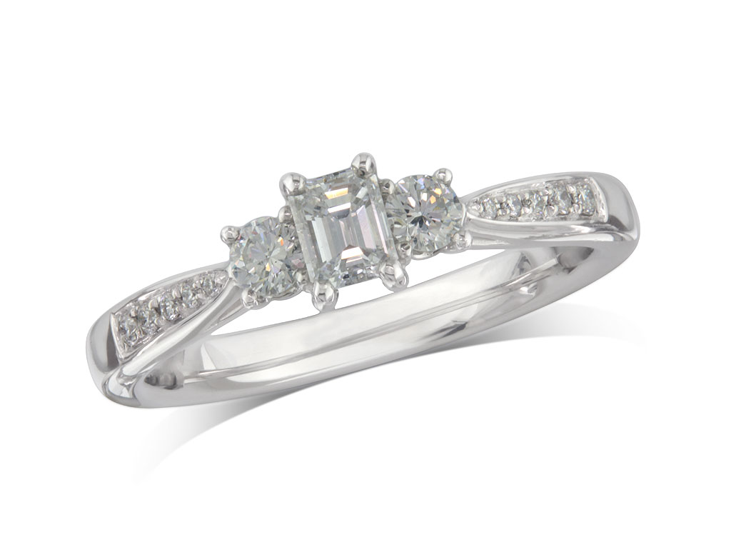 Platinum set three stone diamond engagement ring, with a certificated emerald cut centre in a four claw setting, and one brilliant cut with diamond set shoulders on each side. Perfect fit with a wedding ring. Total diamond weight: 0.45ct.