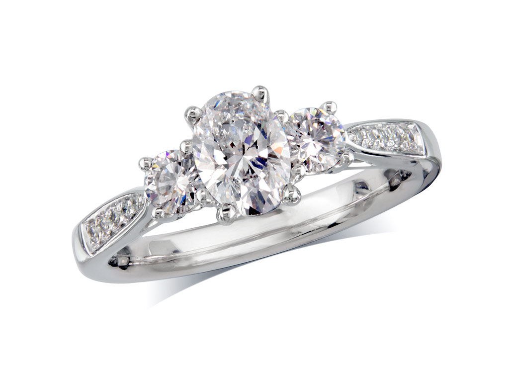 Platinum set three stone diamond engagement ring, with a certificated oval cut centre in a four claw setting, and one brilliant cut with diamond set shoulders on each side. Perfect fit with a wedding ring. Total diamond weight: 1.18ct.