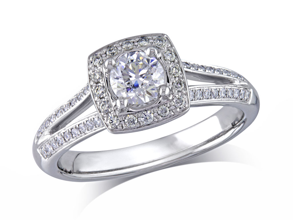 Platinum set diamond engagement ring, with a certificated brilliant cut in a four claw setting, surrounded by a diamond set cluster and split shoulders. Perfect fit with a wedding ring. Total diamond weight: 0.64ct.