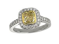 Platinum set diamond cluster engagement ring, with a certificated natural yellow cushion cut centre in a yellow gold rub over setting, surrounded by a diamond set cluster and shoulders. Total diamond weight: 0.74ct.