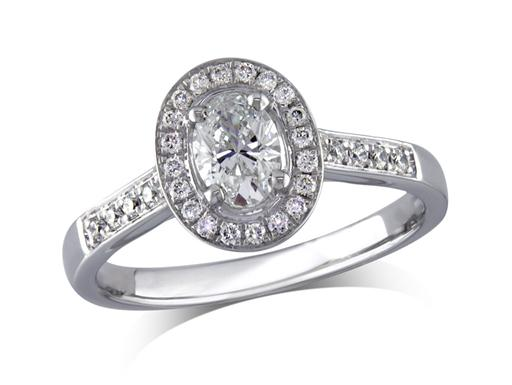 Platinum set diamond ring, with a certificated oval cut centre in a four claw setting, surrounded by a diamond set cluster and shoulders. Perfect fit with a wedding ring. Total diamond weight: 0.70ct
