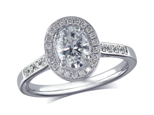 Platinum set diamond ring, with a certificated oval cut centre in a four claw setting, surrounded by a diamond set cluster and shoulders. Perfect fit with a wedding ring. Total diamond weight: 0.94