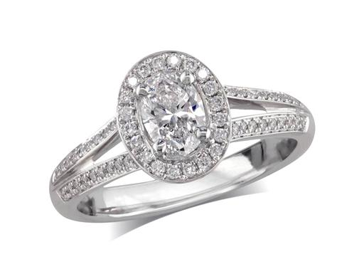 Platinum set diamond engagement ring, with a certificated oval cut in a four claw setting, surrounded by a diamond set cluster and split shoulders. Perfect fit with a wedding ring. Total diamond weight: 0.63ct.
