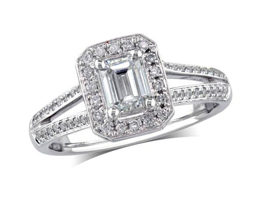 Platinum set diamond engagement ring, with a certificated emerald cut in a four claw setting, surrounded by a diamond set cluster and split shoulders. Perfect fit with a wedding ring. Total diamond weight: 0.75ct.