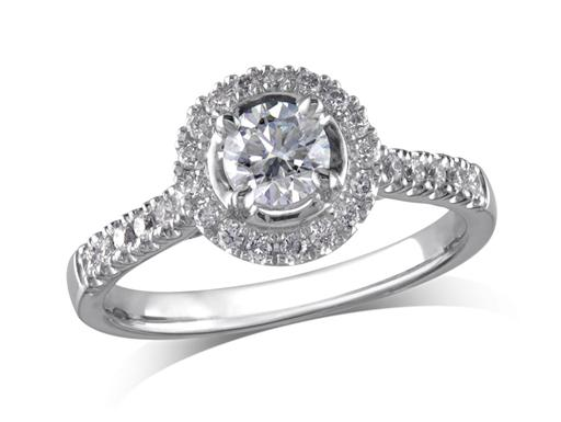 Platinum set diamond ring, with a certificated brilliant cut centre in a four claw setting, surrounded by a diamond set cluster and shoulders. Perfect fit with a wedding ring. Total diamond weight: 0.68ct.