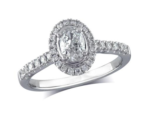 Platinum set diamond ring, with a certificated oval cut centre in a four claw setting, surrounded by a diamond set cluster and shoulders. Perfect fit with a wedding ring. Total diamond weight: 0.61cts