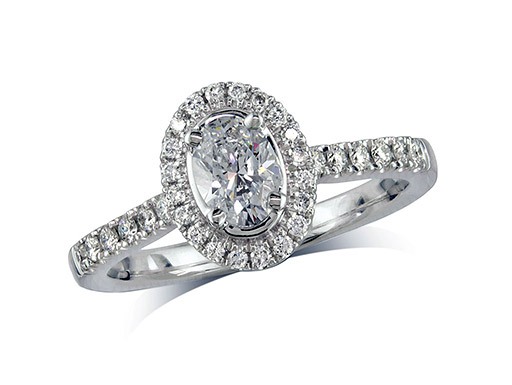 Platinum set diamond ring, with a certificated oval cut centre in a four claw setting, surrounded by a diamond set cluster and shoulders. Perfect fit with a wedding ring. Total diamond weight: 0.77cts