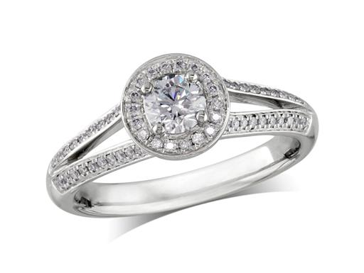 Platinum set diamond engagement ring, with a certificated brilliant cut in a four claw setting, surrounded by a diamond set cluster and split shoulders. Perfect fit with a wedding ring. Total diamond weight: 0.70ct