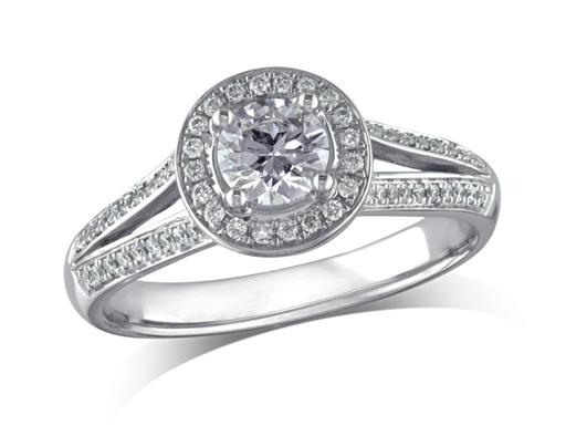 Platinum set diamond engagement ring, with a certificated brilliant cut in a four claw setting, surrounded by a diamond set cluster and split shoulders. Perfect fit with a wedding ring. Total diamond weight: 0.70ct.