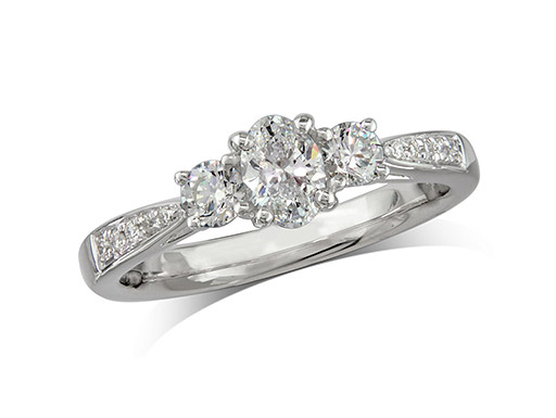 Platinum set three stone diamond engagement ring, with a certificated oval cut centre in a four claw setting, and one brilliant cut with diamond set shoulders on each side. Perfect fit with a wedding ring. Total diamond weight: 0.61ct.