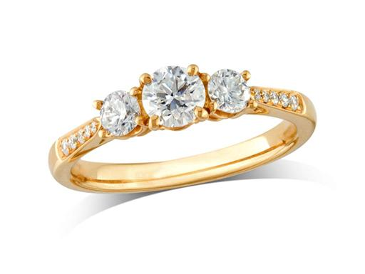 18 carat yellow gold set three stone diamond engagement ring, with a certificated brilliant cut centre in a four claw setting, and one brilliant cut with diamond set shoulders on each side. Perfect fit with a wedding ring. Total diamond weight: 0.70ct