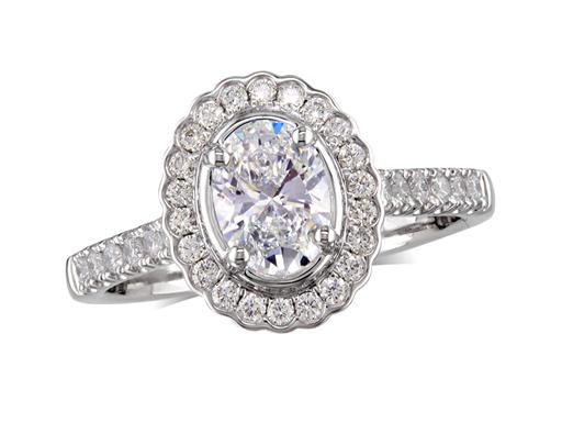 Platinum set diamond cluster engagement ring, with a certified oval cut centre in a four claw setting, with a surrounding diamond set bezel and diamond set shoulders. Perfect fit with a wedding ring. Total cluster diamond weight:0.82