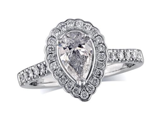 Platinum set diamond ring, with a certificated pear cut centre in a three claw setting, surrounded by a diamond set cluster. Perfect fit with a wedding ring. Total diamond weight: 1.04cts