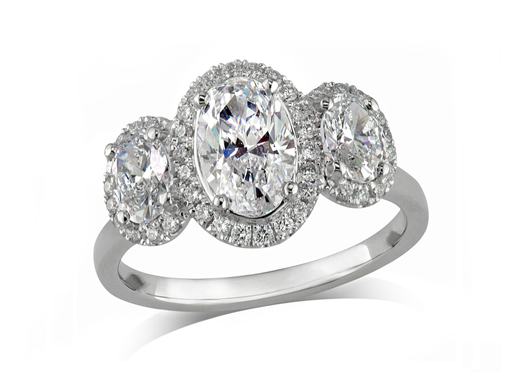 Platinum set diamond three cluster engagement ring, with a certificated oval cut centre in a four claw setting, with a surrounding diamond set bezel and a oval cut diamond on either shoulder each with a diamond set surround. Total cluster diamond weight: 1.31ct.