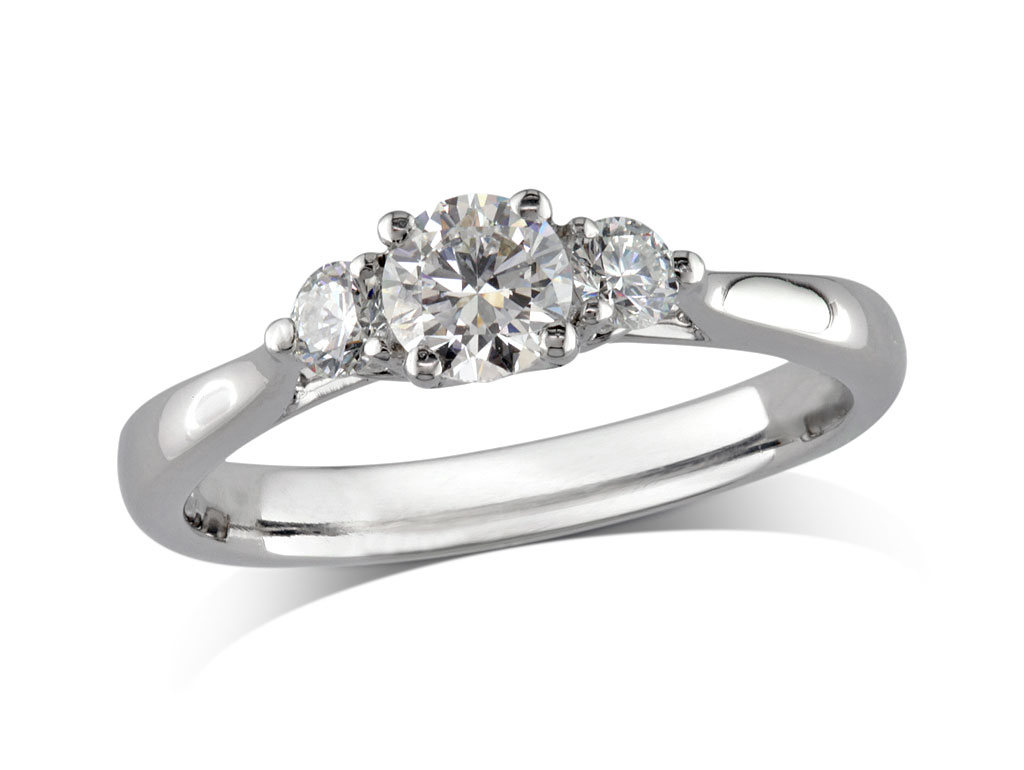 Platinum set three stone diamond engagement ring, with a certificated brilliant cut centre in a four claw setting, and one brilliant cut on each shoulder. Perfect fit with a wedding ring. Total diamond weight: 0.60ct.