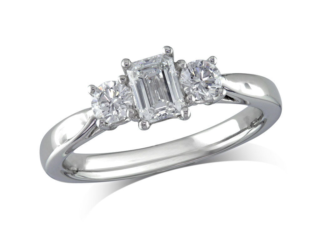 Platinum set three stone diamond engagement ring, with a certificated emerald cut centre in a four claw setting, and one brilliant cut on each shoulder. Perfect fit with a wedding ring. Total diamond weight: 0.82ct.