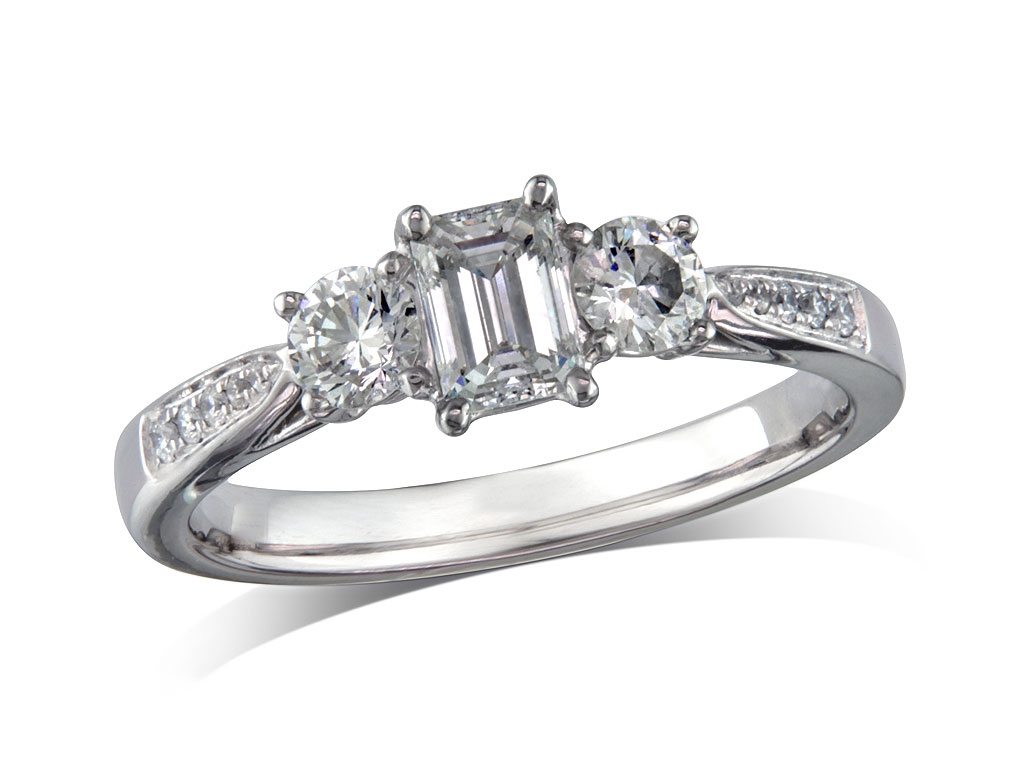 Platinum set three stone diamond engagement ring, with a certificated emerald cut centre in a four claw setting, and one brilliant cut on each side with diamond set shoulders. Perfect fit with a wedding ring. Total diamond weight: 0.64ct.