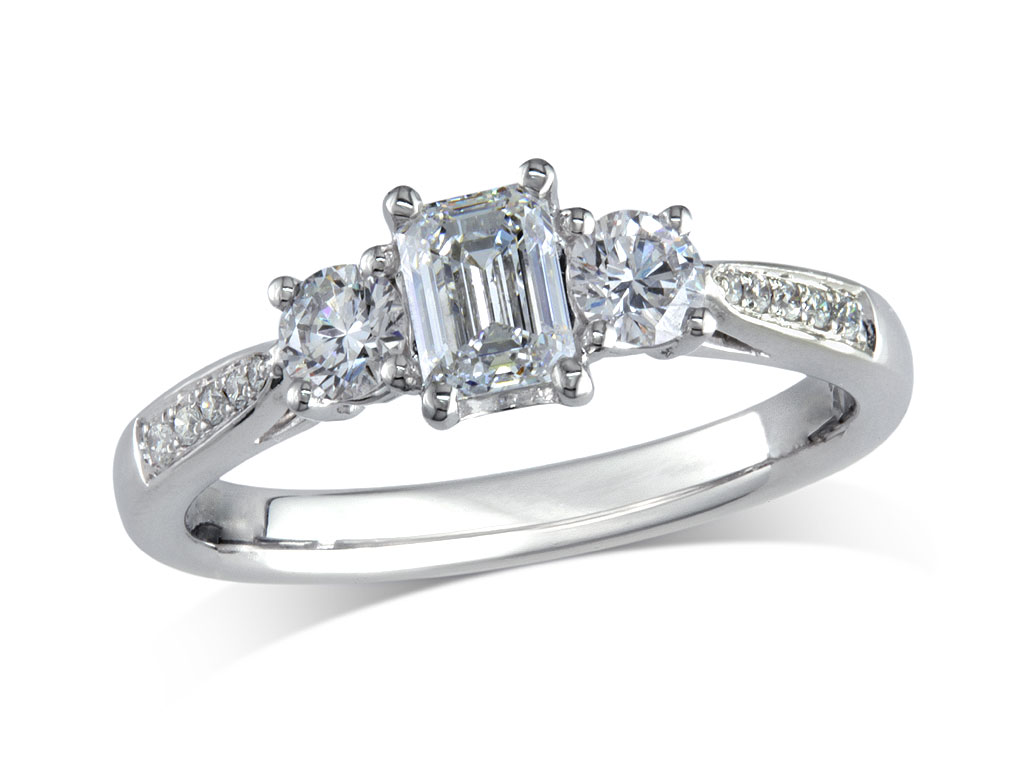 Platinum set three stone diamond engagement ring, with a certificated emerald cut centre in a four claw setting, and one brilliant cut on each side with diamond set shoulders. Perfect fit with a wedding ring. Total diamond weight: 0.96