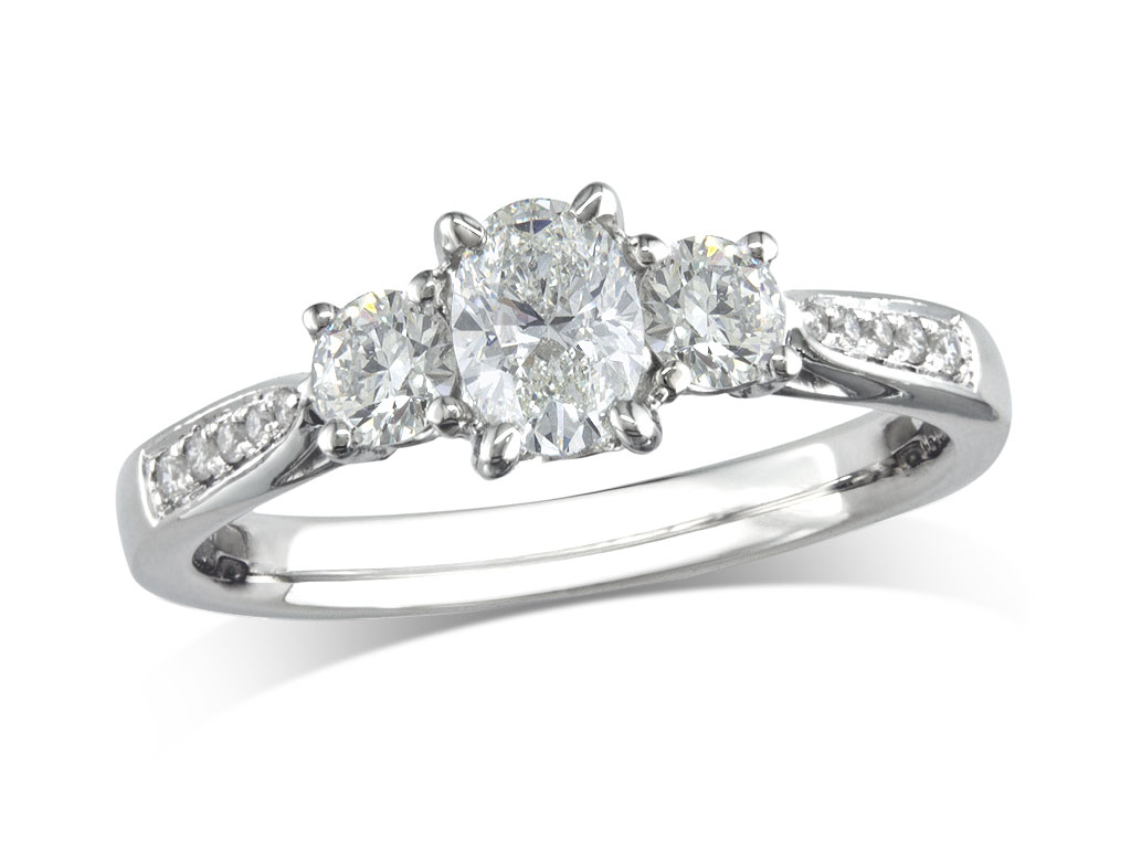 Platinum set three stone diamond engagement ring, with a certificated oval cut centre in a four claw setting, and one brilliant cut with diamond set shoulders on each side. Perfect fit with a wedding ring. Total diamond weight: 0.71ct.