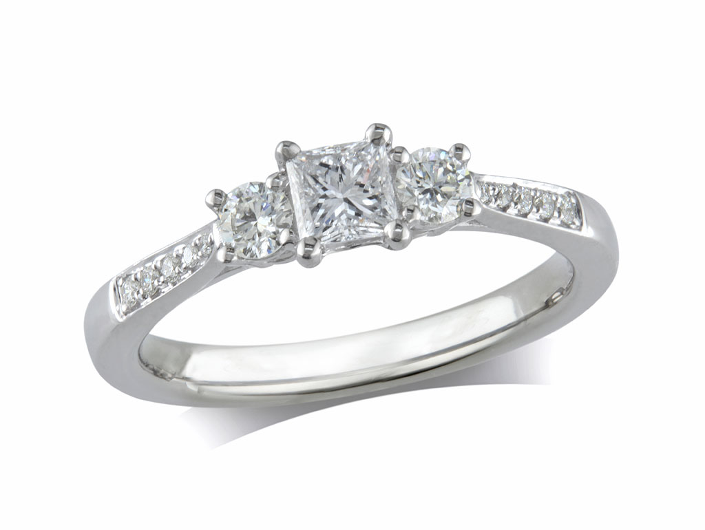 Platinum set three stone diamond engagement ring, with a certificated princess cut centre in a four claw setting, and one brilliant cut on each side with diamond set shoulders. Perfect fit with a wedding ring. Total diamond weight: 0.56ct.