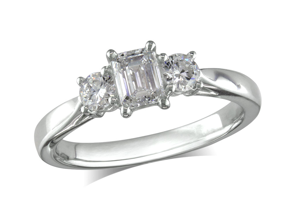 Platinum set three stone diamond engagement ring, with a certificated emerald cut centre in a four claw setting, and one brilliant cut on each shoulder. Perfect fit with a wedding ring. Total diamond weight: 0.87ct.