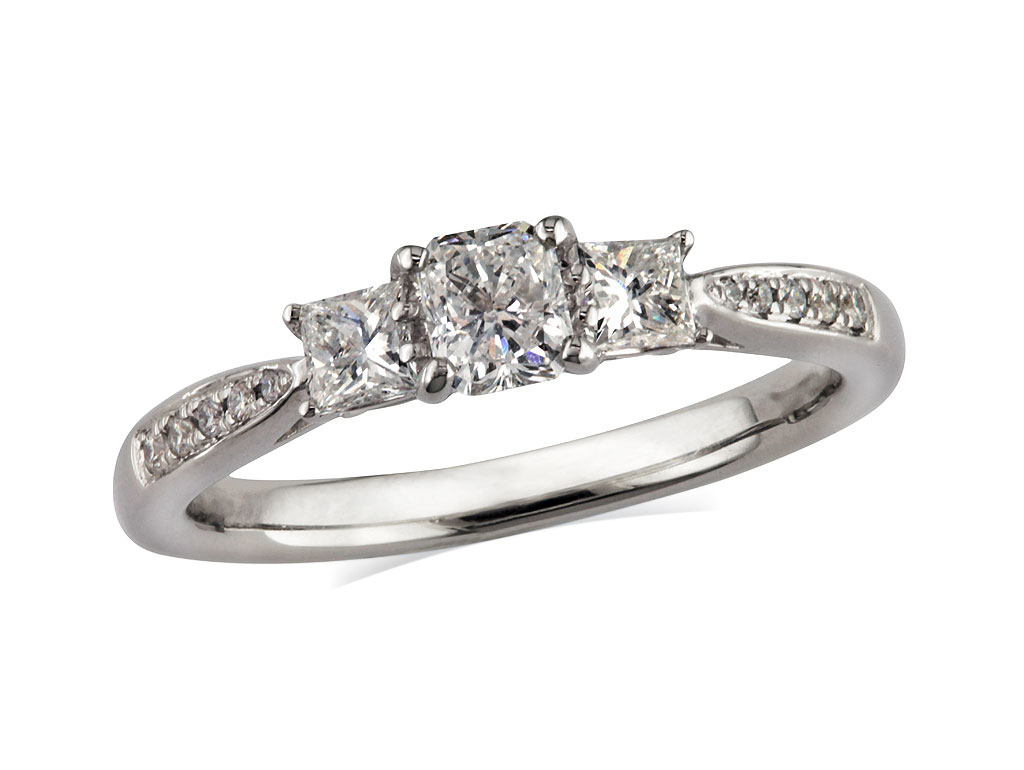 Platinum set three stone diamond engagement ring, with a certificated princess cut centre in a four claw setting, and one princess cut on each side with diamond set shoulders. Perfect fit with a wedding ring. Total diamond weight: 0.60ct.