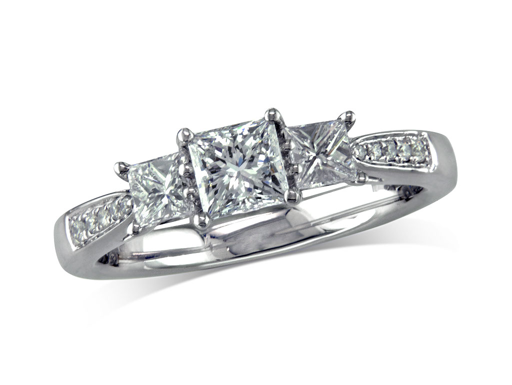 Platinum set three stone diamond engagement ring, with a certificated princess cut centre in a four claw setting, and one brilliant cut on each side with diamond set shoulders. Perfect fit with a wedding ring. Total diamond weight: 1.00ct.