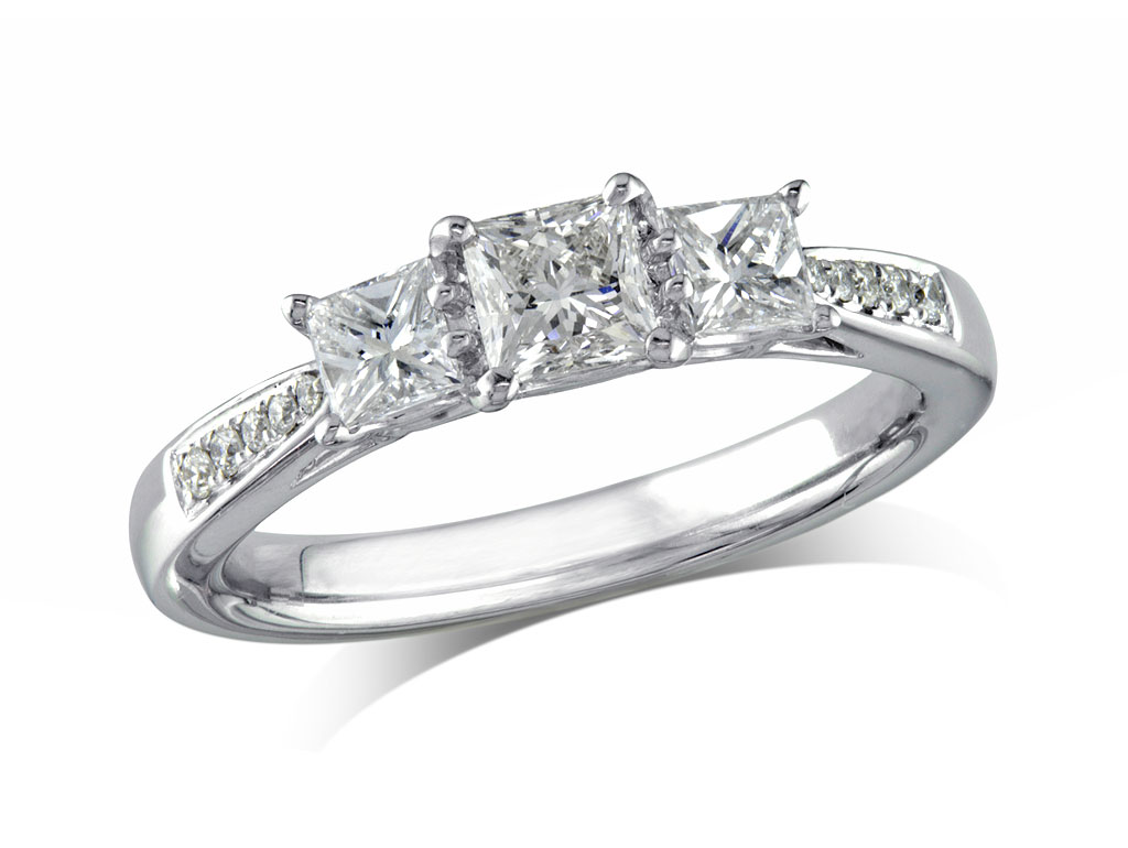 Platinum set three stone diamond engagement ring, with a certificated princess cut centre in a four claw setting, and one princess cut on each side with diamond set shoulders. Total diamond weight: 0.64ct.